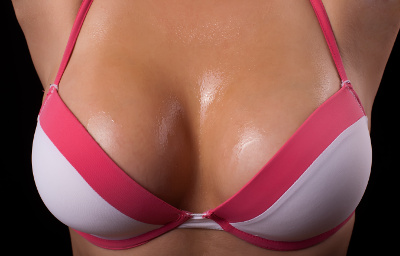 Woman breast in uplift on a black background 1